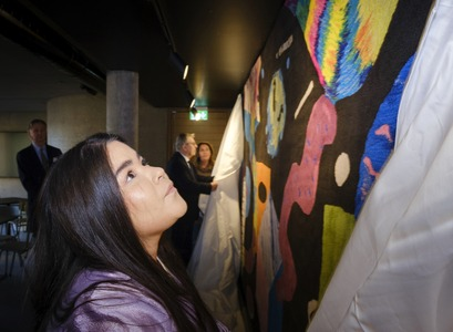Isabel Alejandra Díaz, President of the UI Student Council, unveiles a work of art dedicated to a century of student activism